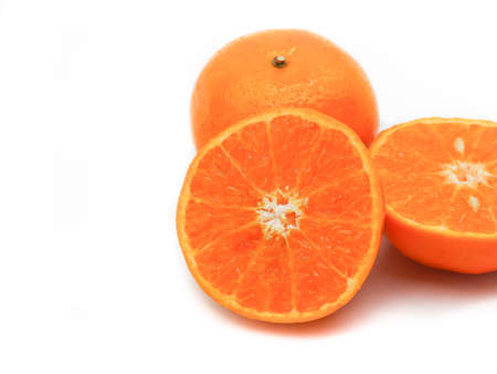Fresh orange fruit cut in half placed on a white background.