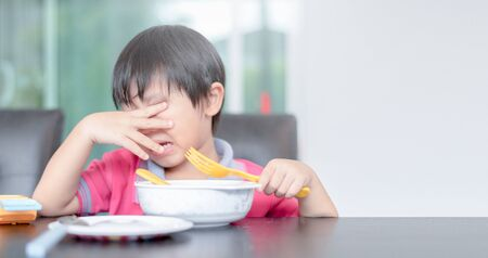asian child boy eating boring food in morning Stockfoto
