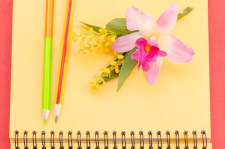 Notebook with pencil and flower orchid photo