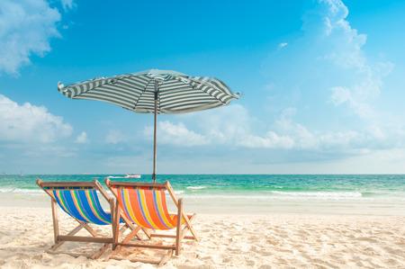Twee stoelen en parasol op het strand