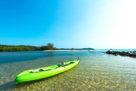 shallow water: Green canoe on shallow water at the beach