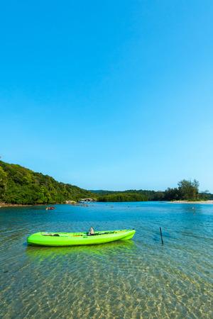 kood: Green canoe on shallow water at the beach