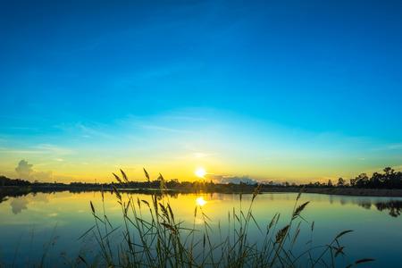 日没の風景と穏やかな湖の青い空 写真素材