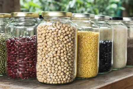 alubias: Cierre de soja en un frasco de vidrio con el grano de color multi