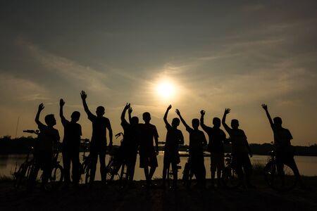 winner: Puesta de sol silueta de niño son la felicidad con la moto ganadora para la salud Foto de archivo