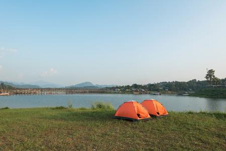 camping pitch: Orange camping tent at the lake Stock Photo