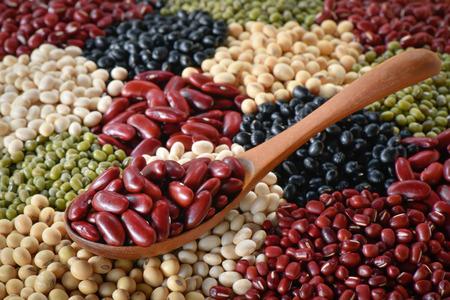 Shift Adzuki bean with wooden spoon on various legumes background