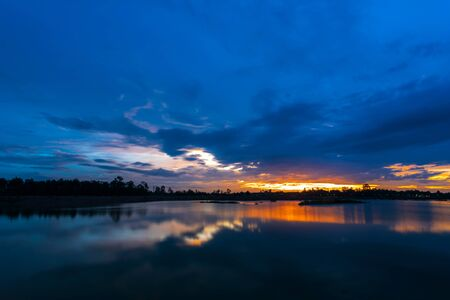 eventide: Breathtaking sunset with blue sky over lake Stock Photo