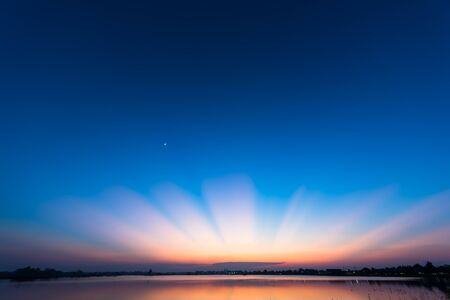 eventide: Wonderful sun ray after sunset  over lake, Breathtaking landscape with sunligth after sunset, Beautiful sunset with blue sky Stock Photo
