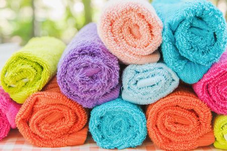 Closeup multicolor towels with nature blur background at the spa club