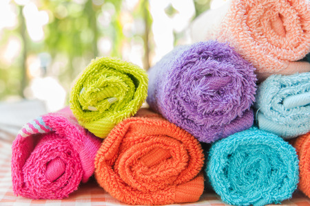 convolute: Roll of Multicolor towels on table cloth with nature blur background Stock Photo