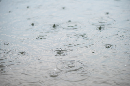 Raindrop impact on rippling water surface Stock Photo