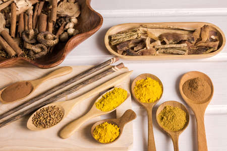 Different herbal and spice in wooden scoop on the table, Various ingredient in container for cooking flat lay on plank Stock Photo