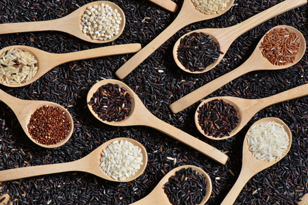 Top view different rice on wooden scoop with black riceberry background, Various rice organic on wooden spoon collection Archivio Fotografico