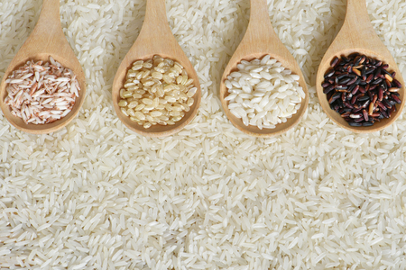 Top view different rice on wooden scoop with jasmine rice background, Various rice organic on wooden spoon collection