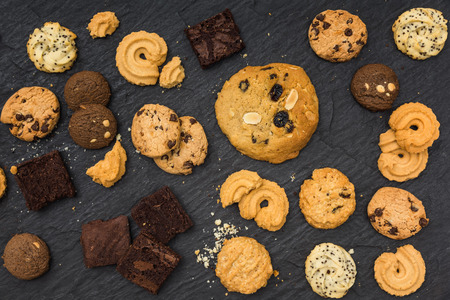 Top view different cookies on table top, Flat lay of various cookies on black stone for background Standard-Bild - 109886901
