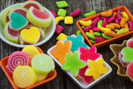 Various colorful sugary candy in container on old wooden plank Standard-Bild - 132005017
