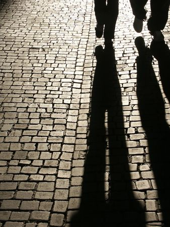 city alley: Two people shadows walking on a cobbled street.