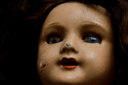 Closeup of an old damaged doll. Shallow DOF, focus on the eyes. High contrast. photo