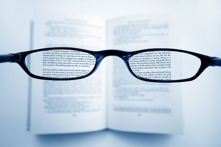 restoring: A pair of glasses above a book, in the lenses, all is clear, outside, is blured. Note to the inspectors, the text is a classic from Voltaire, XVII, The Philosophys Dictionnary Stock Photo