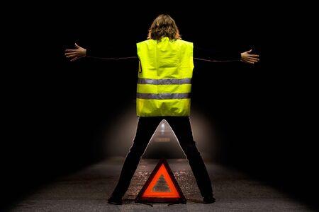 Une jeune fille portant un gilet de sécurité fluo essayer d'arrêter une voiture sur une route la nuit.