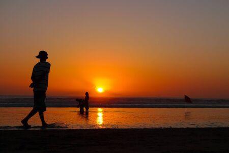 sunshades: A young man walking on the beach at sunset, Kuta Beach, Bali