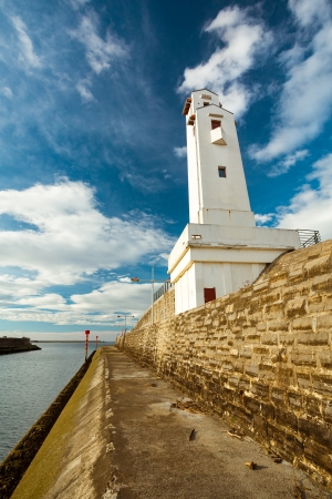 semaphore: The Ciboure lighthouse, at the channel entry, under a vibrant blue sky full of fluffy clouds