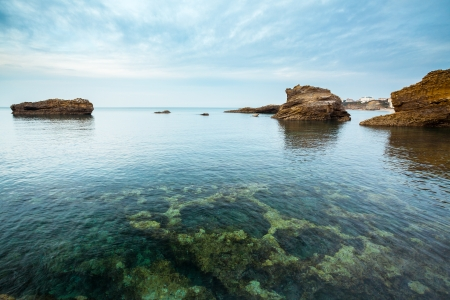 pays: Seascape from Biarritz, France, Pays Basque  Rocks under a creamy sky  Clean transparent water