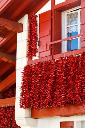 chiles picantes: Una fachada típica vasca con racimos de secado de pimientos rojos