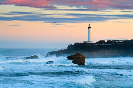 pays: The iconic lighthouse of Biarritz, under a pinkish morning sky  Big waves hitting the rocks