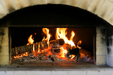 A fire that has been lit inside a pizza oven.
