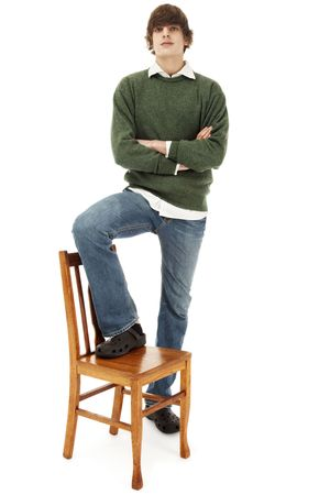 Photo of a confident young man, standing on a wooden chair