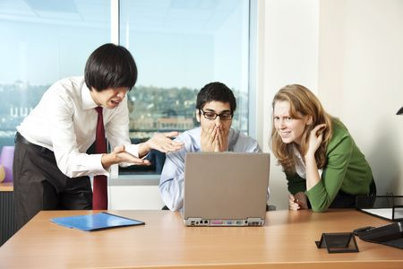 Three business colleagues distressed by what they see on a laptop computer screen. photo