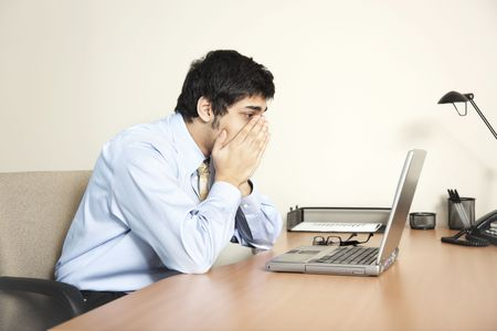 Businessman looking at his laptop computer screen as if faced with a big problem Stock Photo