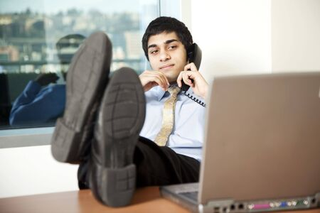 Young businessman reading his computer screen while talking on the phone, feet up on the desk. photo