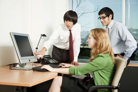 Three business colleagues analyzing data on computer screen photo