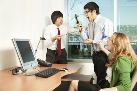 Photo of a businessman losing his temper on a phonecall in front of his colleagues. Stock Photo