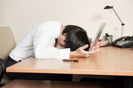 Photo of a young businessman with his face smashed into his laptop keyboard. Stock Photo