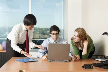 Photo of a young business team sitting around a laptop computer looking confused and upset.