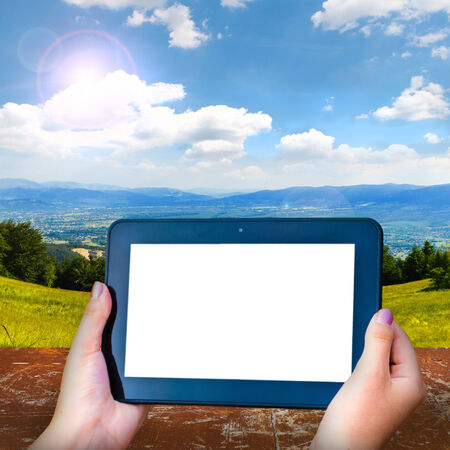 Black Tablet with a blank screen on the mountain landscape photo