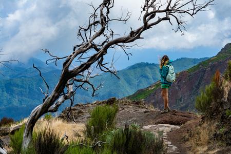Woman traveler at Madeira mountain path between Pico Ruivo and Pico Areeiro Stock Photo
