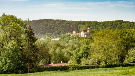 Scenic spring landscape with leafy green woodland and a view to a distant historic church or cathedral over the treetops Standard-Bild