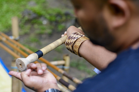 Man showing tourist where to insert poisoned stick into blowpipe