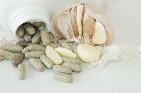 A bottle of organic garlic pills along with natural raw garlic