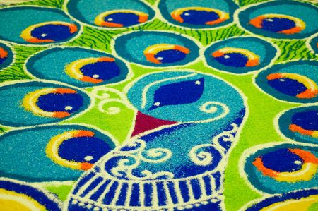 India folk art (rangoli) of a peacock using colored rice put together on the floor