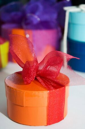 A present wrapped with a ribbon for a festive season with more present boxes in the background. See gallery for more.