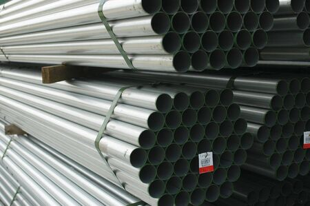 Stacked metal pipes at a construction site Stock Photo
