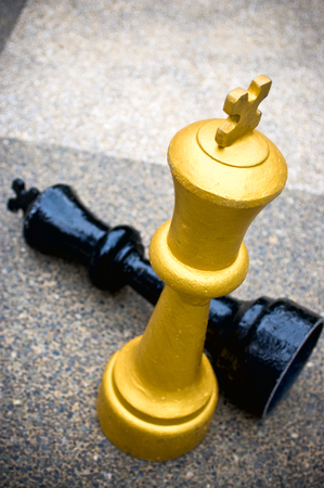invade: A black chess king piece checkmate by a gold chess piece