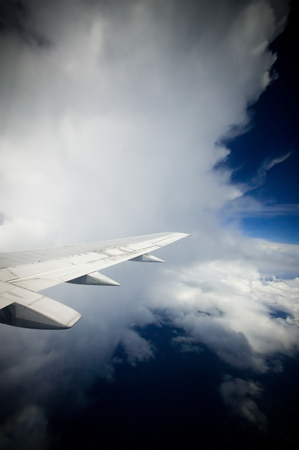 Plane flying into a large white cloud in the air