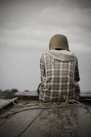 A poor man sitting at the helm of a boat deep in thought
